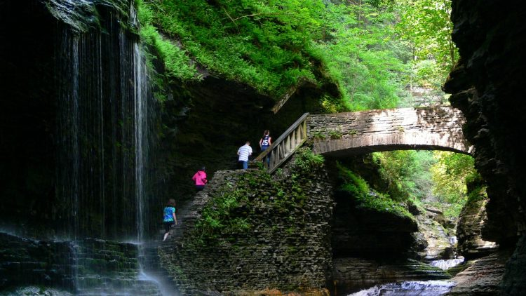 People hiking over bridge in Watkins Glen State Park - Things to do in UpState New York