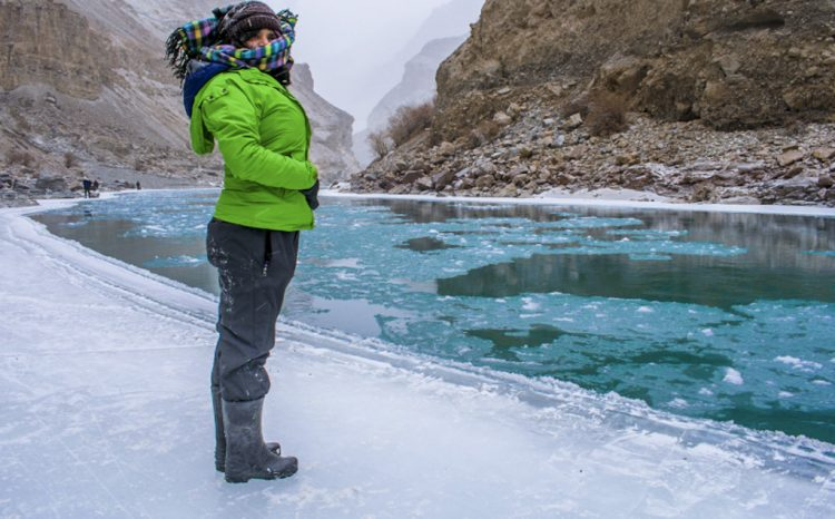 Woman standing in front of Icy River on Chadar Trek in Ladakh, India