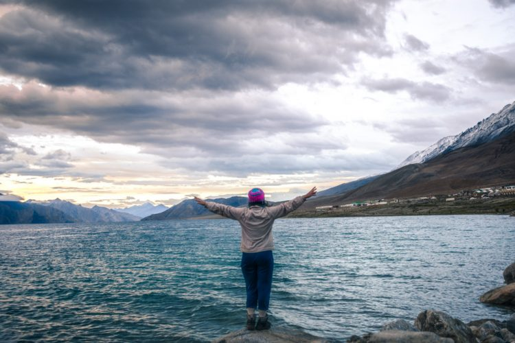 Woman standing on the shore of Pangong Lake - Places to see in Ladakh