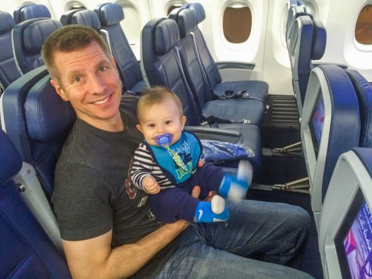 Man holding his baby with a smile on his face while sitting on a plane