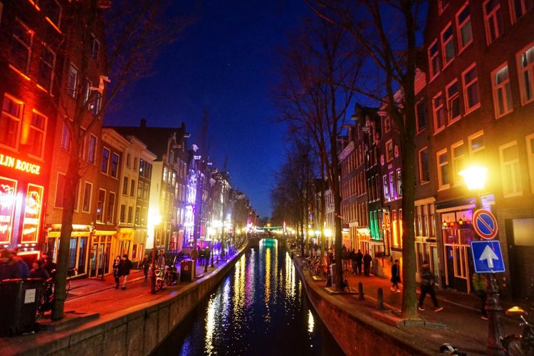 Bright colorful lights along the streets of Amsterdam's Red Light District at night