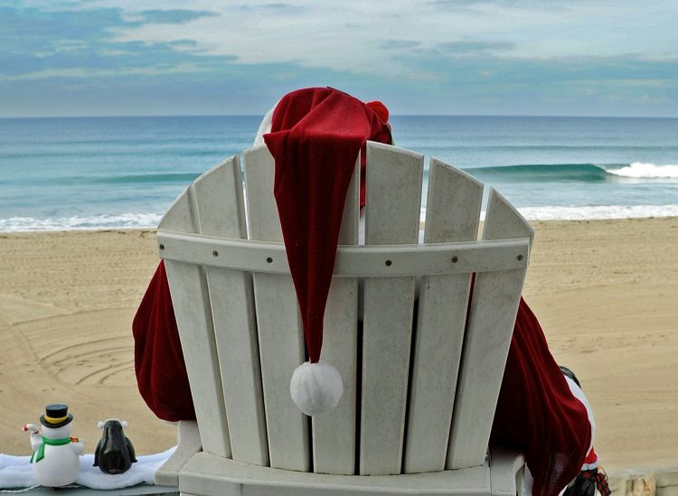 Santa Claus sitting on beach chair on the beach, in front of the ocean