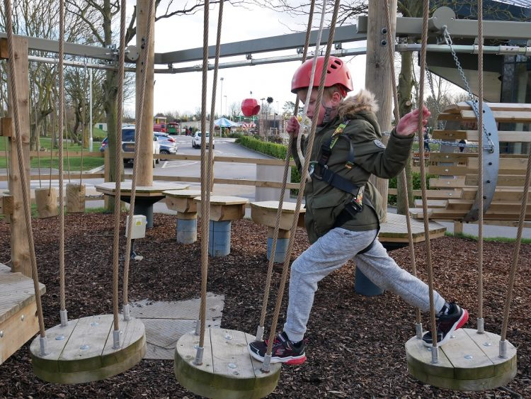 Small child with a red helmet on, playing on an adventure playground on a gloomy day