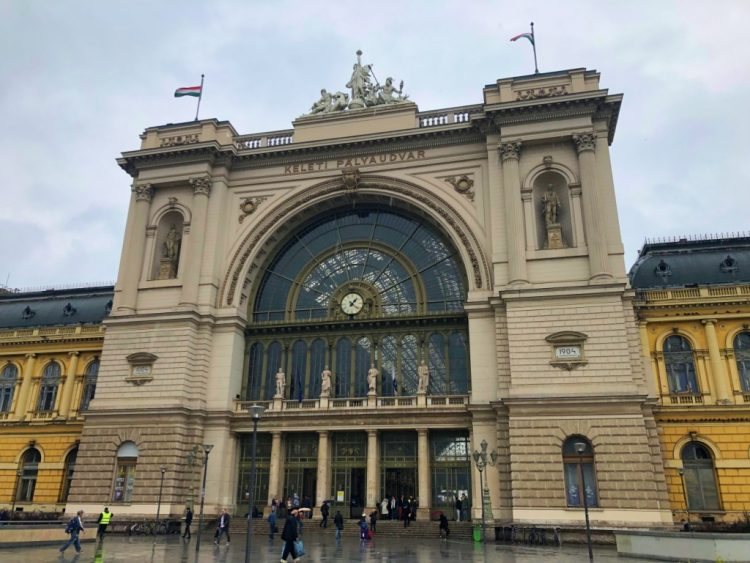Lovely archaic Budapest train station with people coming in and out on a slightly cloudy day