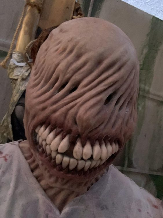 Scare actress in a special effects mask that twists the skin over the eyes and accents the gross yellow teeth