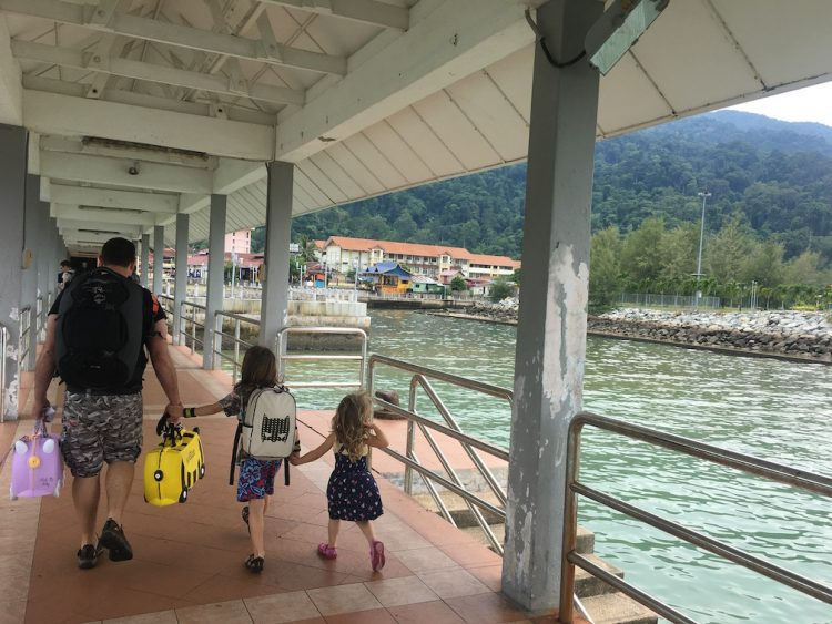 A father holding hands with his daughter who's holding her little sister's hand on a dock overlooking the beautiful blue water as a boat passes