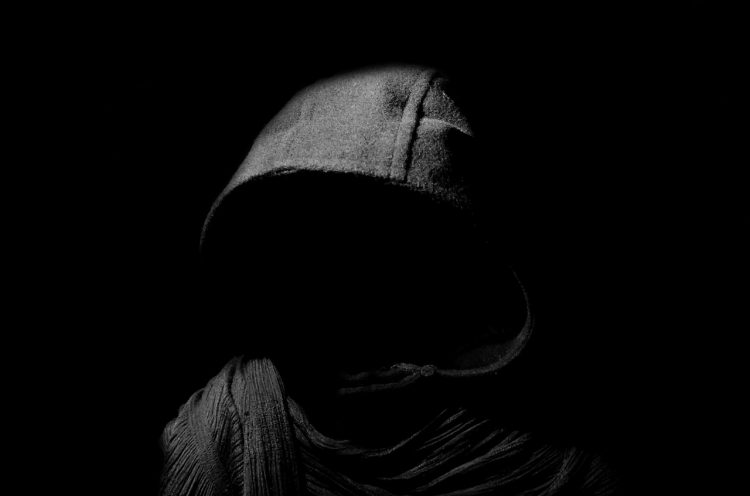 Scare actor dressed as a faceless grim reaper in the dark