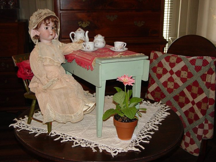 Creepy doll sitting at an otherwise empty table for a tea party