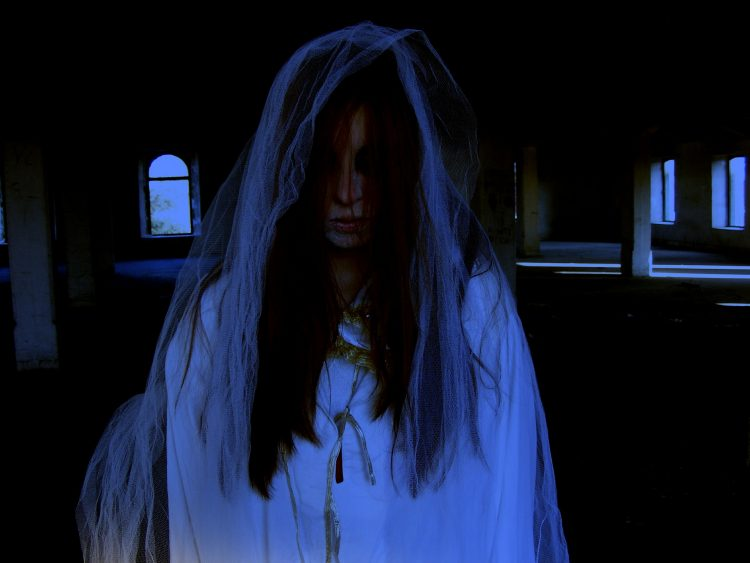 Ghostly woman dressed in white with a veil sadly draped over her head as blood drips from her forehead
