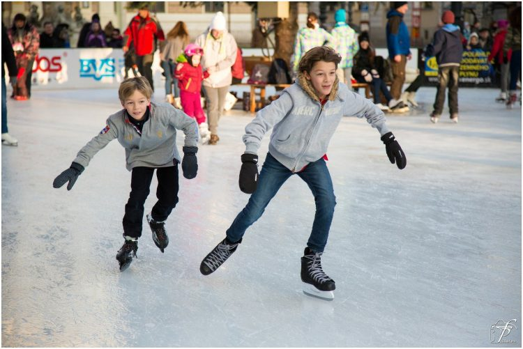 Two boys racing on ice skates in an arena with other people idly skating behind them