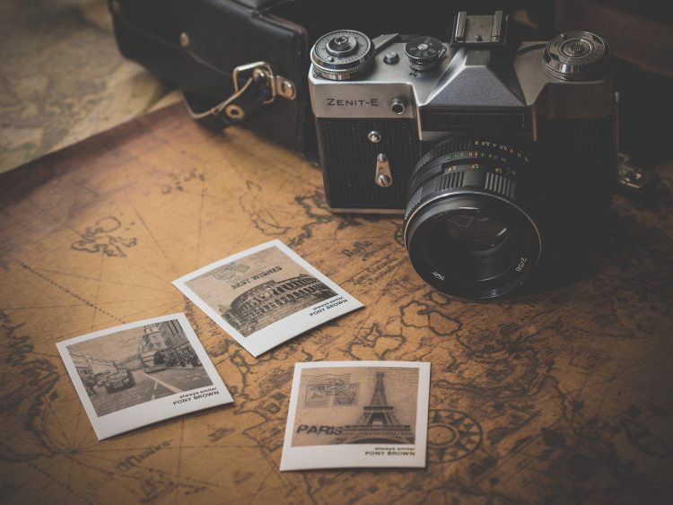 Polaroids of European destinations and a camera on top of a world map