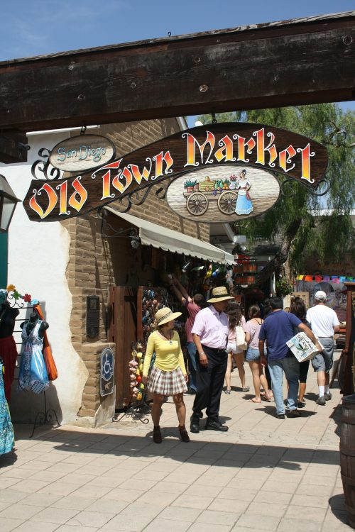 """People wandering around San Diego's Old Town with the sign saying """"Old Town Market"""" overhead"""