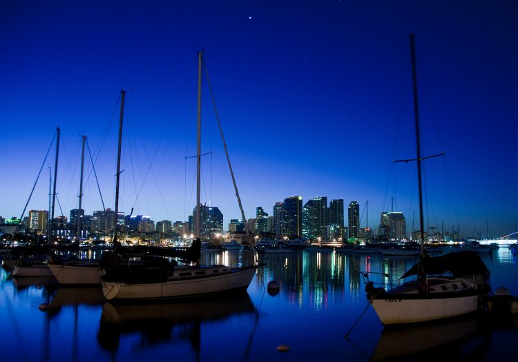 Boats floating in the San Diego bay with the sparkling city scape in the background