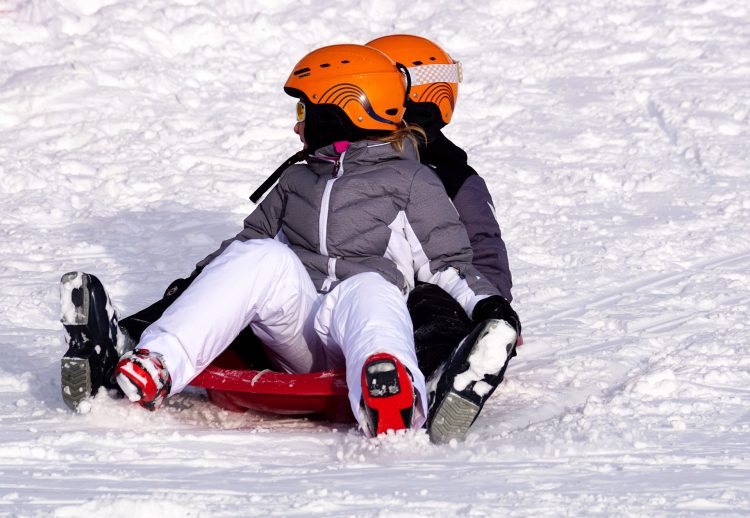 Two kids together sliding down an icy slope on a red tube
