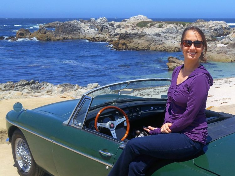 Woman sitting on a green convertible on the cliffside coast